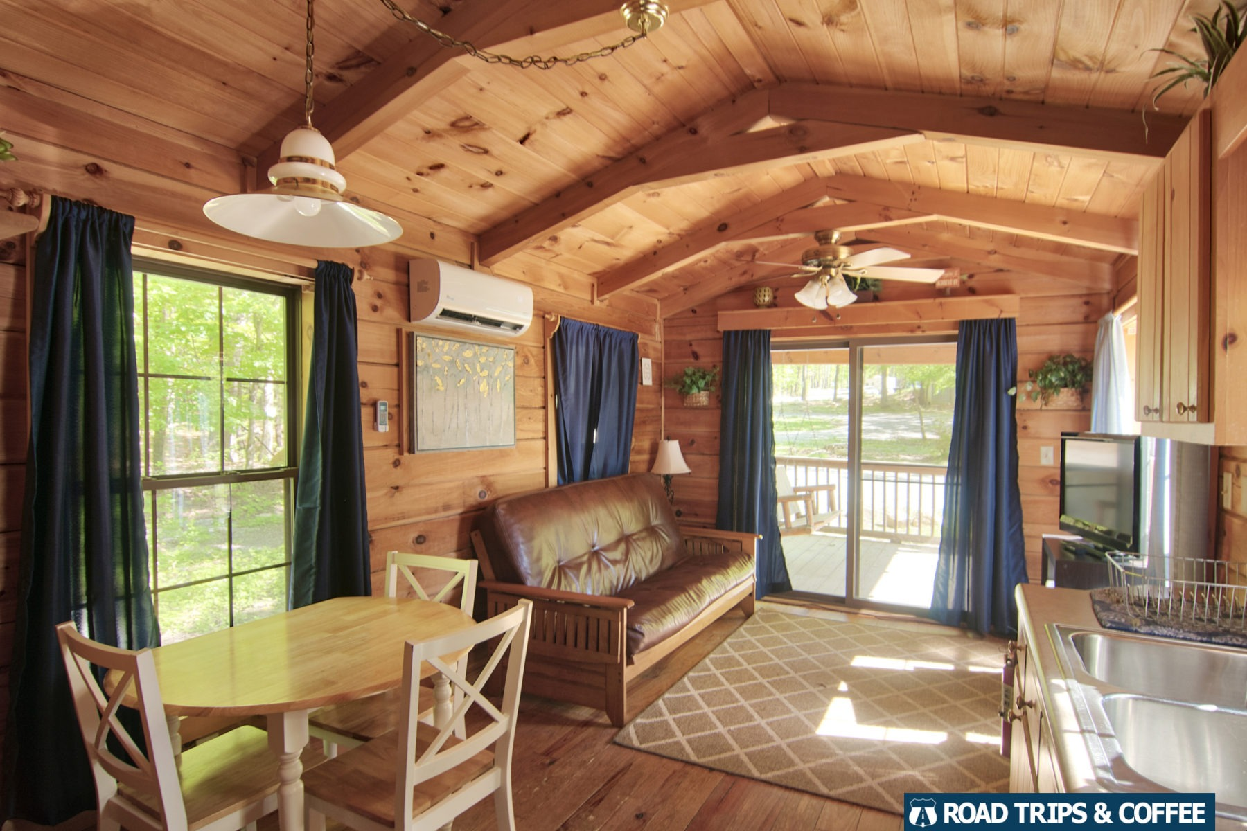 A small cabin with couch, dining room table, and full kitchen at Wytheville KOA in Virginia