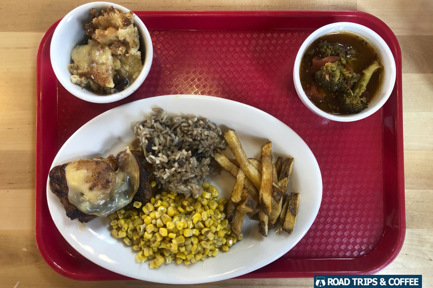 A dinner tray loaded with baked chicken, corn, rice, and banana pudding from the Open Door Cafe in Wytheville, Virginia