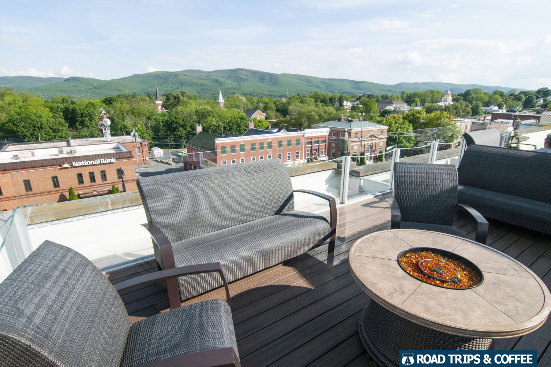 Wicker furniture and a fire pit table on the rooftop terrace The Perch at the Bolling Wilson Hotel in Wytheville, Virginia