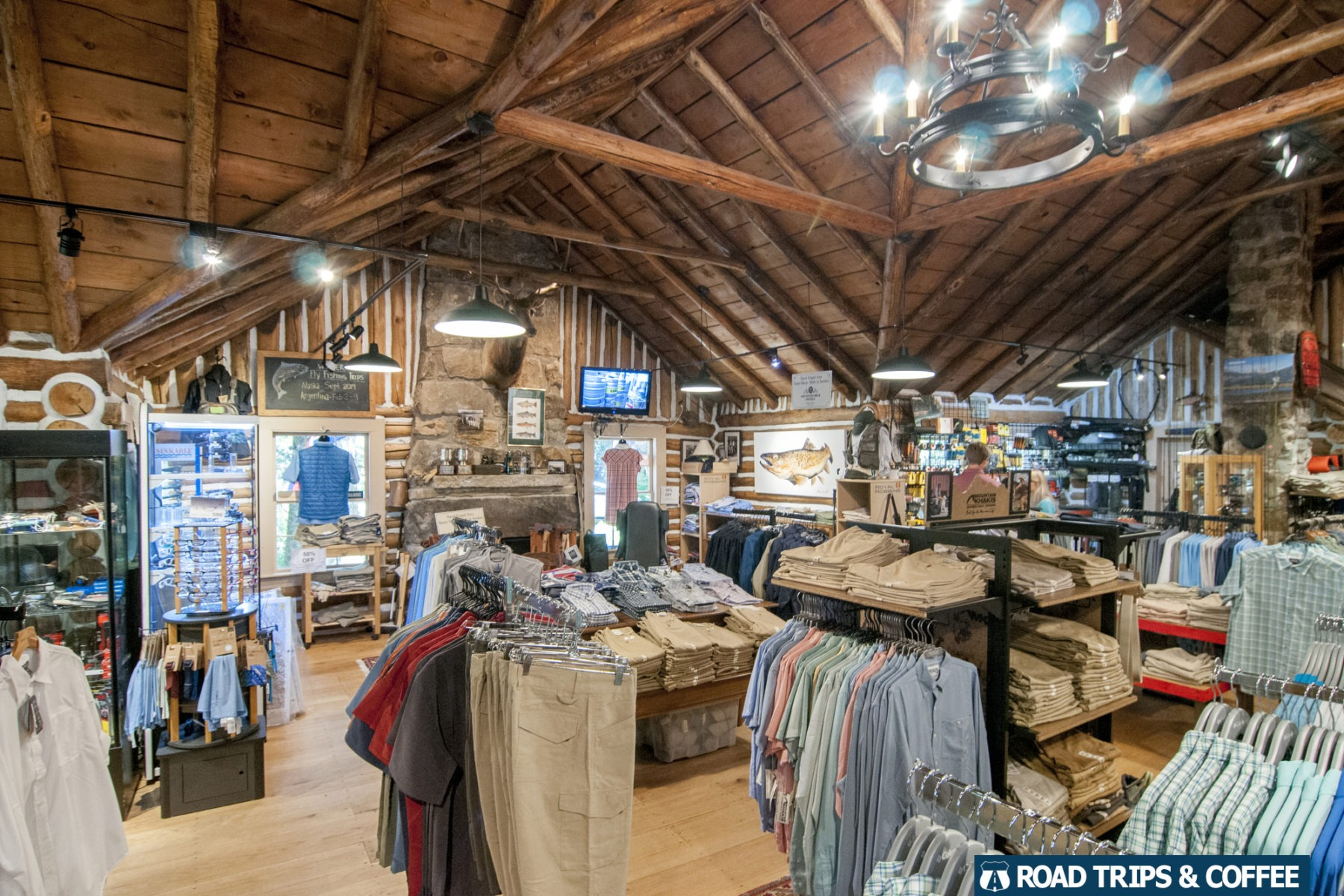 Outdoor clothing spread across racks and gear hang from the insides of a log cabin at Highland Hiker in Highlands, North Carolina