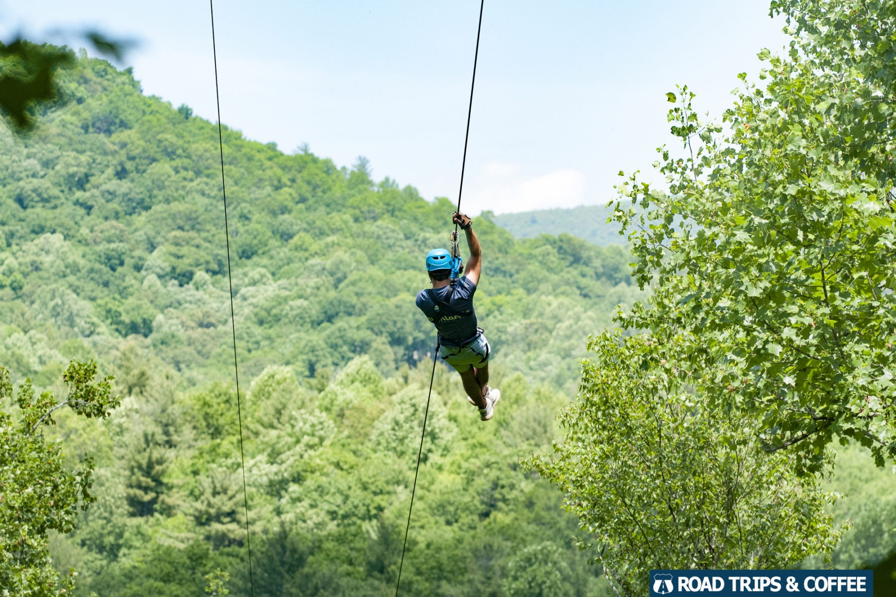 A lone person ziplines down a long line with views of the mountains in all directions at the Highlands Aerial Park in Highlands, North Carolina