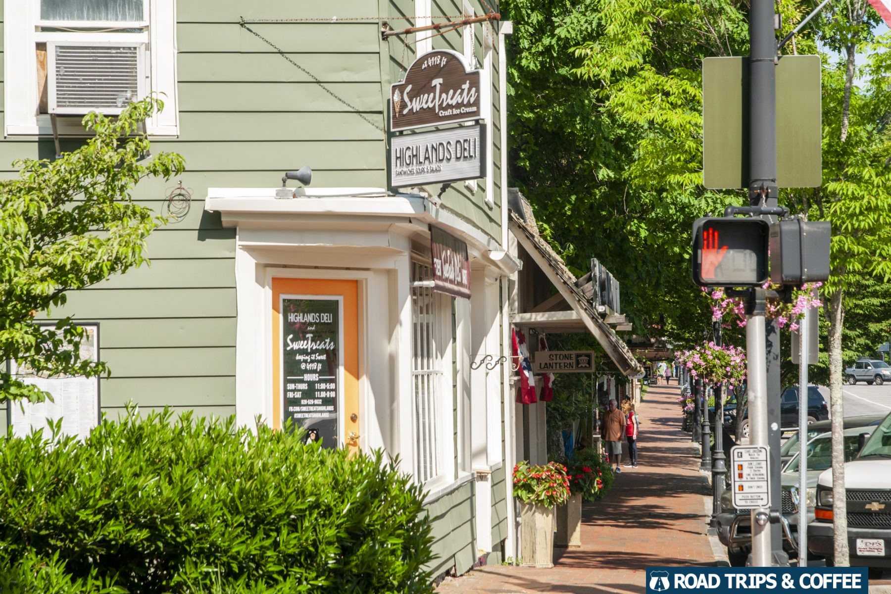 A brick sidewalk stretches along Main Street past several small shops in downtonw Highlands, North Carolina
