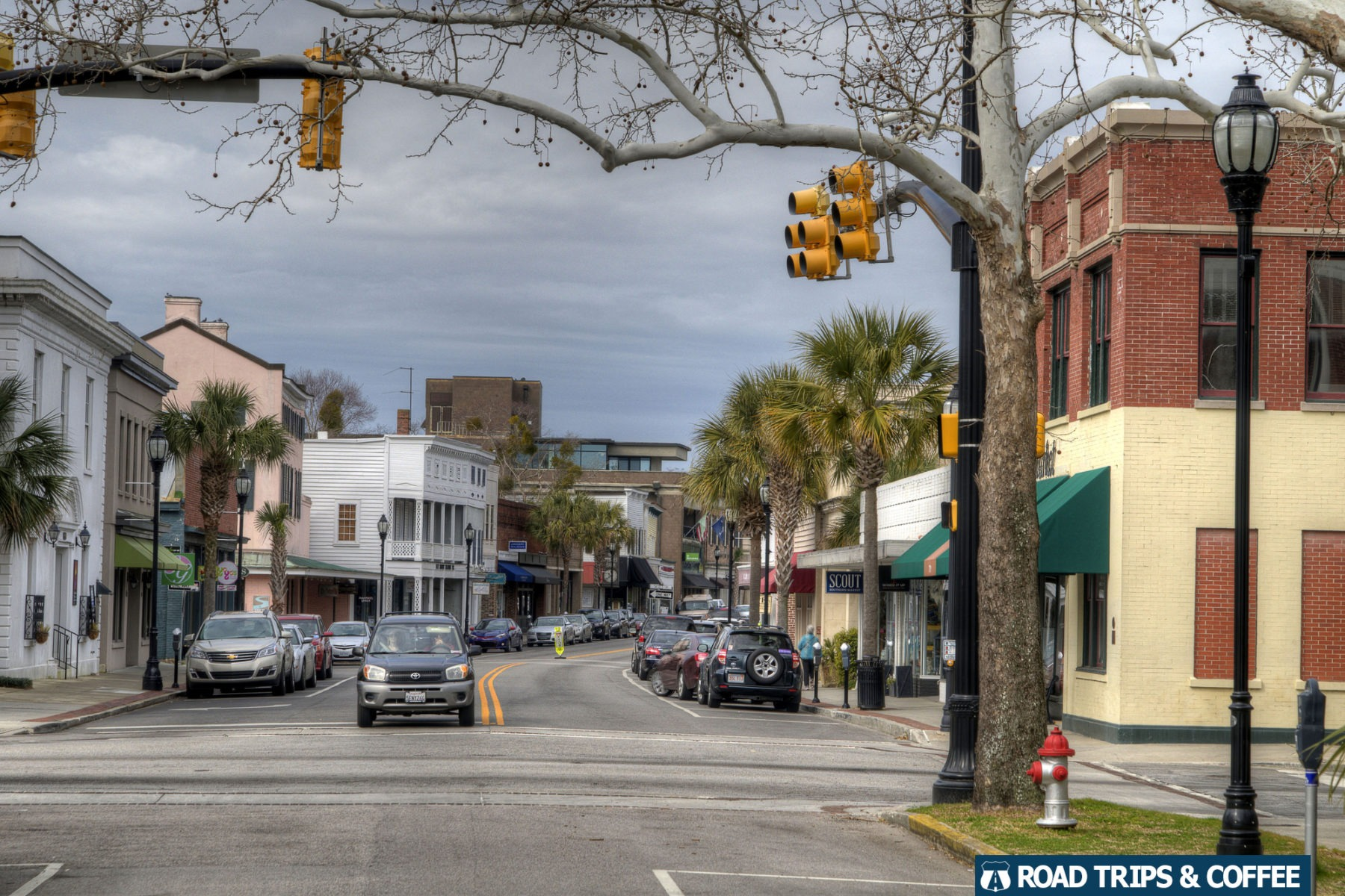 Cars line Bay Street along with palm trees and wide sidwealks through the middle of Beaufort, South Carolina