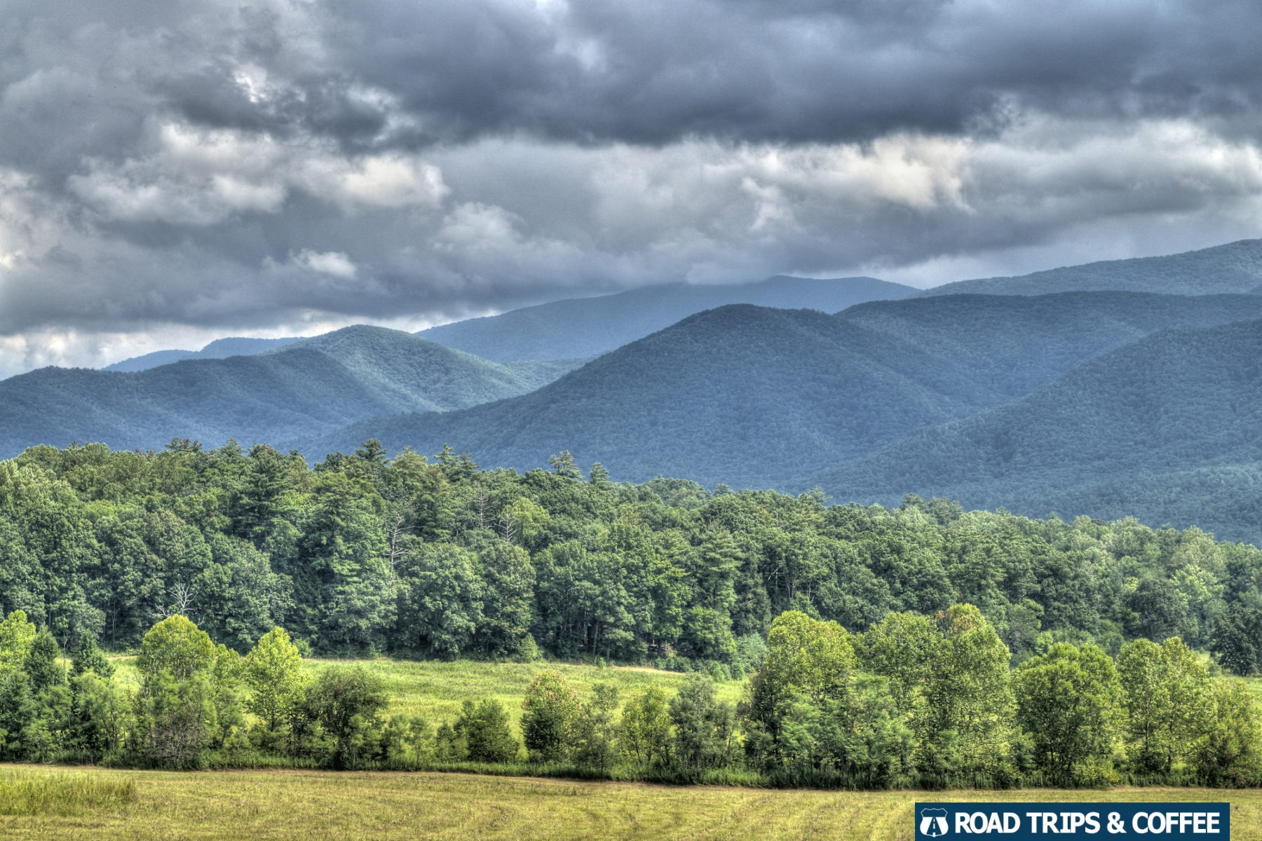 Clouds hang over the lush green landscape and distant mountains at Cades Cove in the Great Smoky Mountains National Park