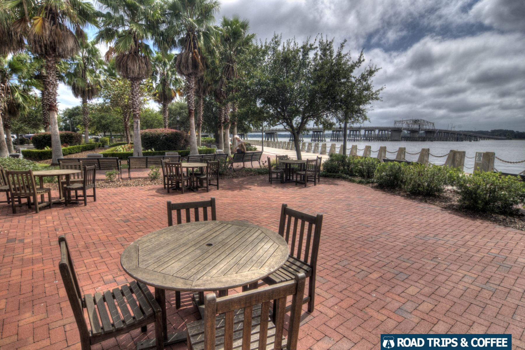 Several sets of wooden tables and chairs on a brick patio at Henry C. Chambers Waterfront Park in Beaufort, South Carolina