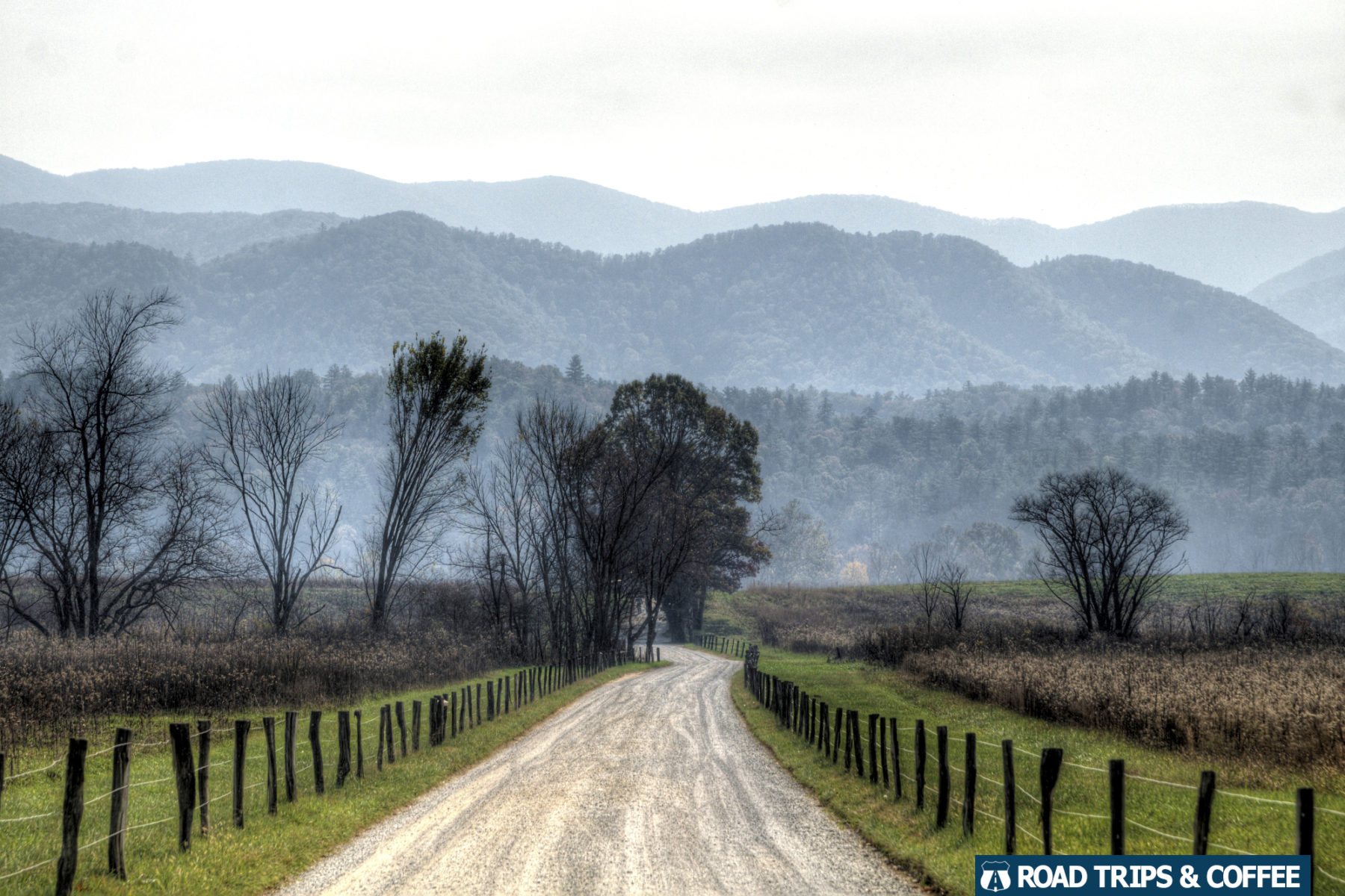 A wide gravel road with a rustic fence on either side and mountains in the distance at Cades Cove in the Great Smoky Mountains National Park