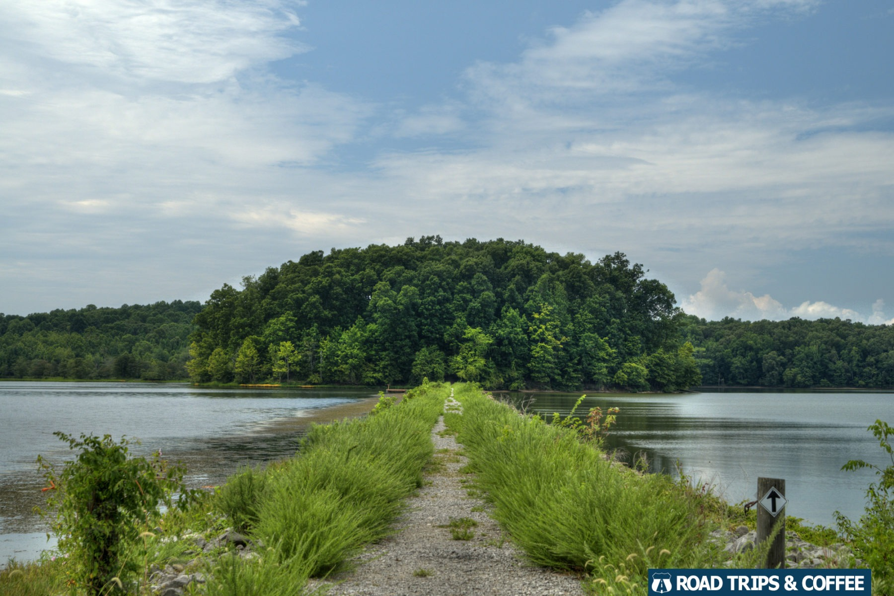 A gravel trail crosses an earthen dam toward a dense forest at Land Between the Lakes National Recreation Area